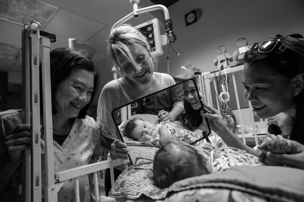 En la UCI neonatal del Hospital Infantil de Texas en Houston, Lucas Guidry, de cinco meses, observa cómo su madre, Sydney (en el centro), sostiene un espejo. Los niños que nacen prematuros o con una enfermedad tienen riesgo de sufrir retrasos cognitivos. Foto: Lynn Johnson